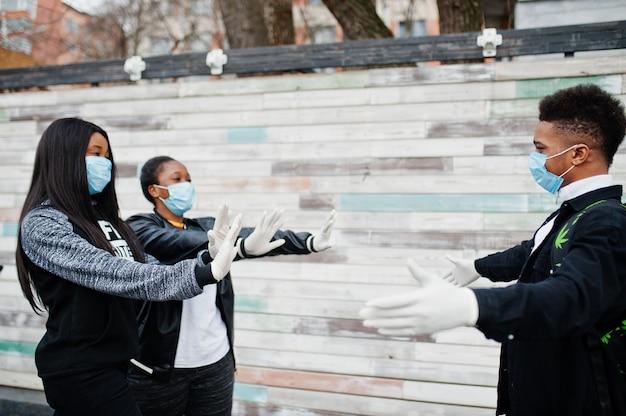 Группа в составе африканские друзья друзей нося медицинские маски защищает от карантина вируса коронавируса инфекций и заболеваний.