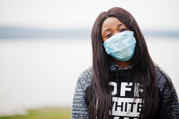 医療マスクを身に着けている公園のアフリカの少女は、コロナウイルスウイルス検疫の感染や病気から保護します。