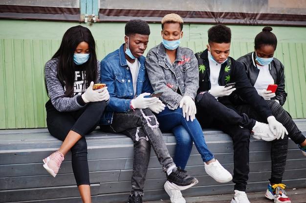 Группа африканских подростков друзей, сидящих с телефонами, в медицинских масках защищает от инфекций и болезней коронавирусный вирус карантина.