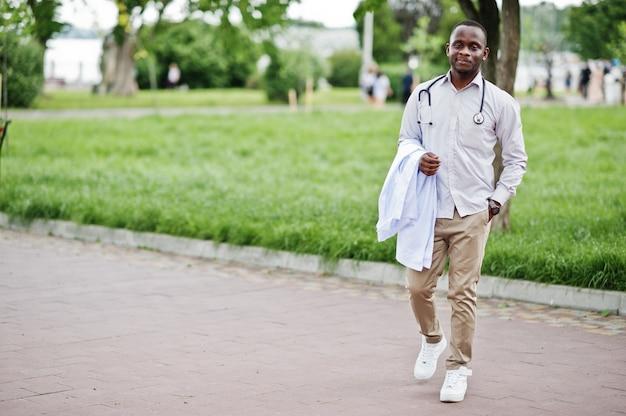 Пальто молодого афро-американского мужского владения доктора белое в наличии при представленный стетоскоп внешний.