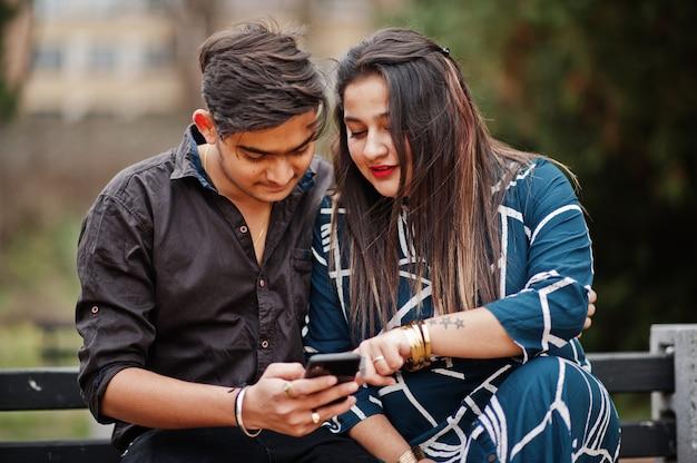 インドのカップルが屋外でポーズをとって、一緒にベンチに座って、携帯電話を見て