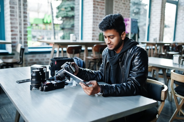 Умный молодой азиатский фотограф человека работая с таблеткой во время сидеть на кафе