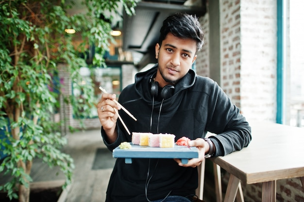 Вскользь и стильный молодой азиатский человек с наушниками на кафе есть суши