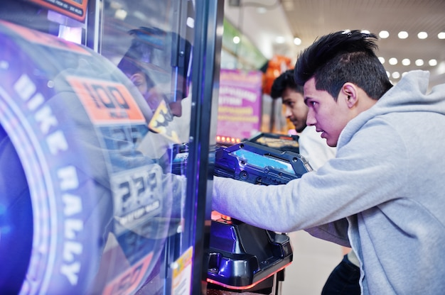 Два азиатских парня соревнуются на игровом автомате-симуляторе