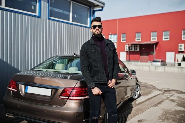 Модный бородатый молодой человек позирует на улице с большой машиной