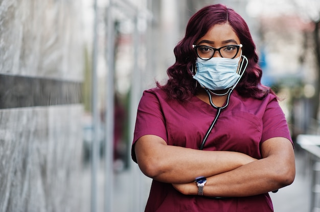 Афро-американский женский доктор на красной форме лаборатории в защитной лицевой маске. медицина, профессия и здравоохранение концепции. остановить коронавирусную инфекцию.