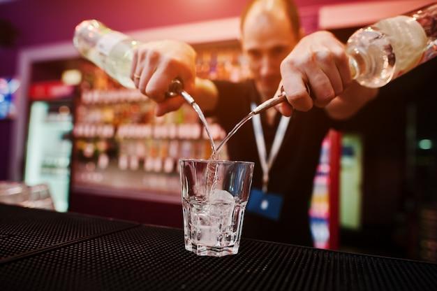 Бармен держит бутылку и наливает коктейль в баре