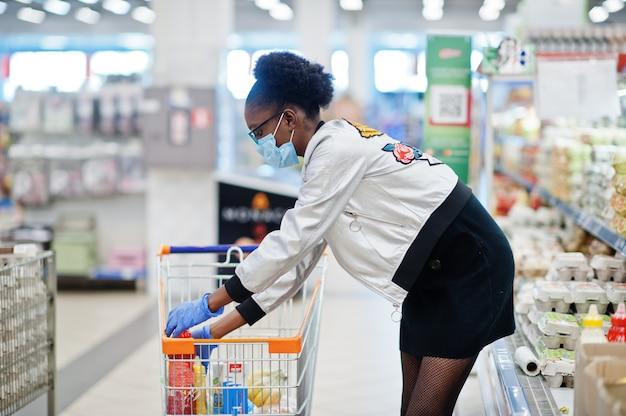 使い捨て医療マスクとコロナウイルスパンデミアの発生中にスーパーで買い物の手袋を着ている女性。