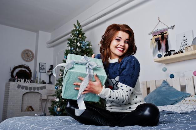 Свитер носки девушки теплый сидя на кровати против дерева нового года с коробкой настоящих моментов на руках на студии. счастливые зимние каникулы концепция.