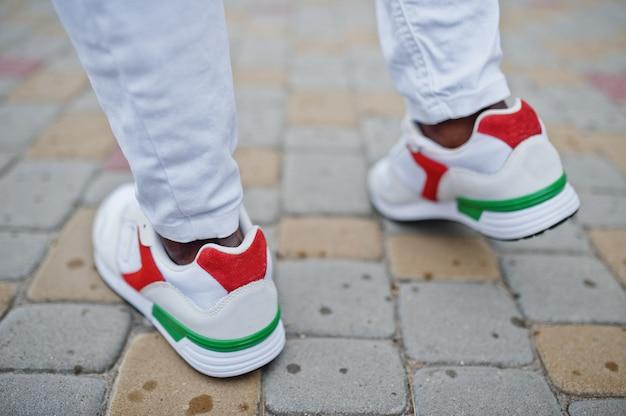白いズボンでアフリカ人のスニーカーを閉じます。