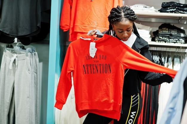スウェットシャツの棚に対してスポーツウェアモールで買い物をするトラックスーツのアフリカ系アメリカ人の女性。スポーツ店のテーマ。