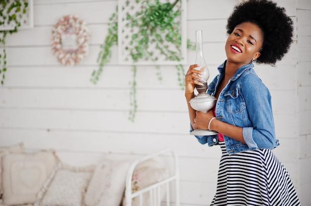 白い部屋で提起されたスカートとジーンズのジャケットにアフロの髪を着て魅力的なアフリカ系アメリカ人女性。ファッショナブルなブラックモデルは、古いガソリンランプを保持します。