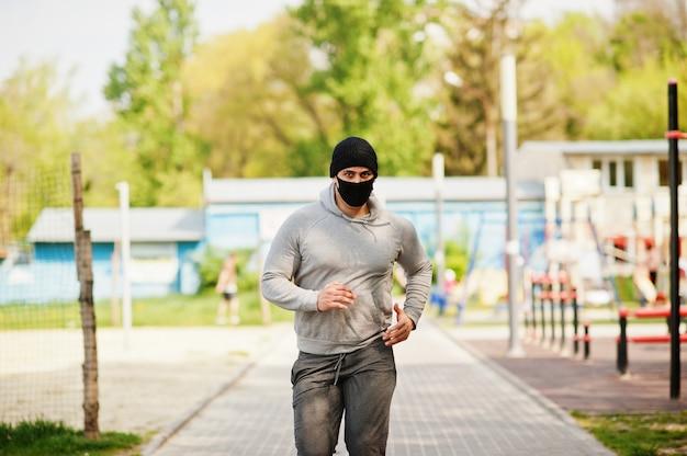 Человек спорт портрета арабский в черной медицинской лицевой маске бежит внешнее во время карантина коронавируса.