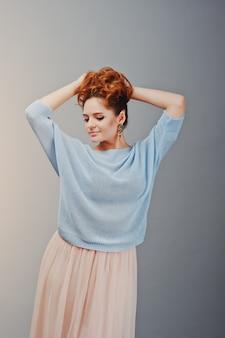 Портрет молодой рыжеволосой кудрявой девушки в синей блузке и розовой юбке