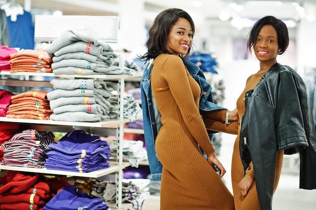Две модели женщины в коричневом платье туники позировали в магазине одежды бутик