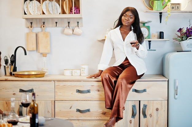 彼女のロマンチックなデートでキッチンでワインを飲むアフロアメリカンの女性。