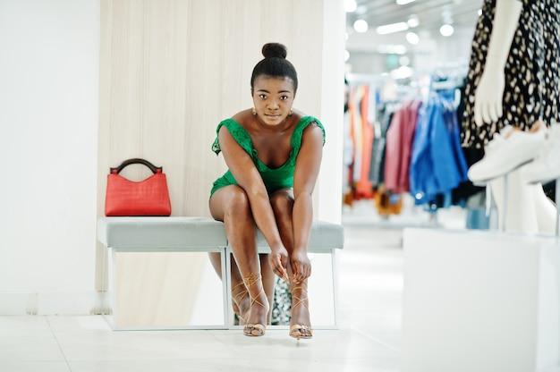 緑のコンビドレス衣料品店でのショッピングでファッショナブルでセクシーなアフロの若い女性。彼女は座ってハイヒールを履いています。