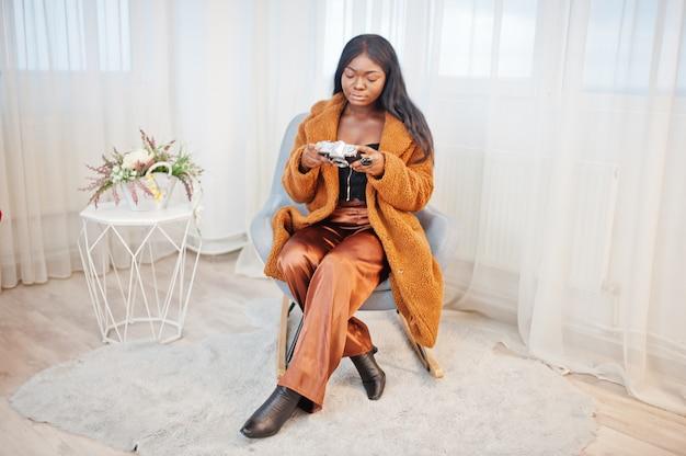 椅子に座っている部屋で提起され、古いビンテージ写真を保持しているオレンジ色のコートを着たスタイリッシュなアフリカ系アメリカ人女性