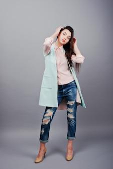 ピンクのブラウス、ターコイズブルーのジャケット、破れたジーンズ、クリーム色の靴を着て全身肖像画若いブルネットの少女
