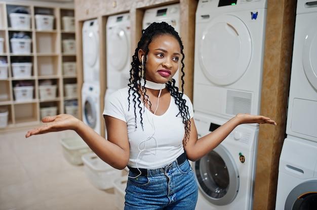 セルフサービスのランドリーで洗濯機に近い悲しい、失望したアフリカ系アメリカ人の女性。