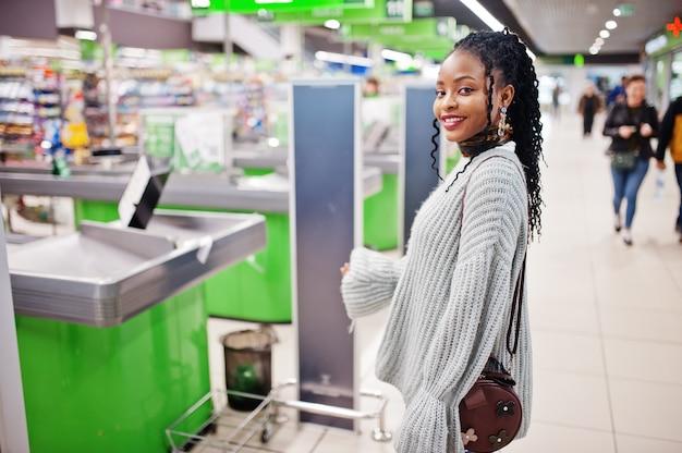 セーターを着たアフリカの女性とレジ係に対してスーパーマーケットでポーズをとったジーンズ。
