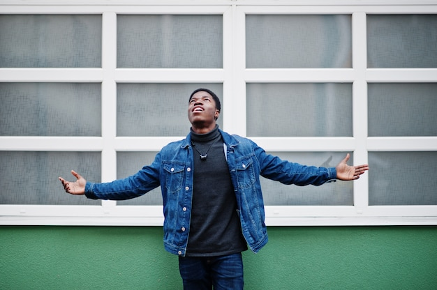 アフリカのナイジェリア人の男は屋外の緑と白の壁に手を上げる