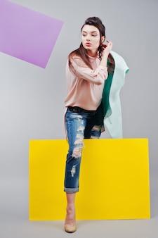 座っている、灰色の背景と黄色と紫のバナーに緑の空白の広告板を保持している美しい少女の完全な長さ