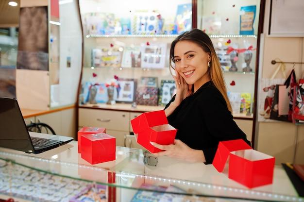 若い白人女性の売り手の肖像画は、赤いギフトボックスを保持します。キャンディのお土産屋の中小企業。
