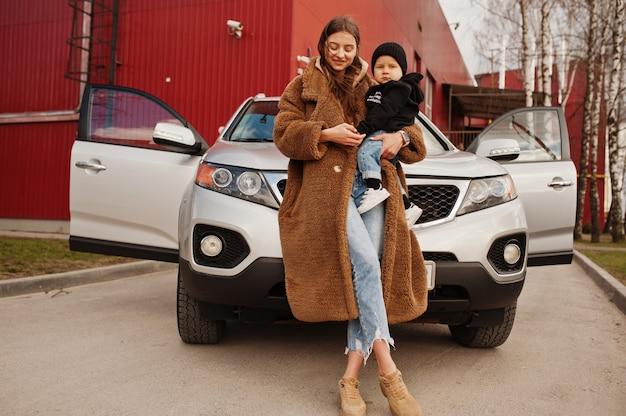 Молодая мать и ребенок стоят возле внедорожника. концепция безопасного вождения.