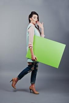 Маленькая девочка с удивленной стороной держит зеленый чистый лист бумаги. молодая усмехаясь женщина показывает пустую карточку. девушка с длинным портретом волос изолированная на серой предпосылке.