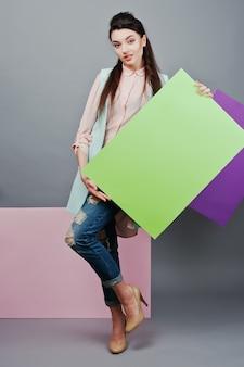 灰色の背景とピンクと紫のバナー上の緑の空白の広告板で、美しい少女の完全な長さ
