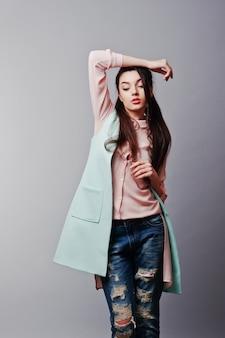 ピンクのブラウス、ターコイズブルーのジャケット、破れたジーンズを着ている若いブルネットの少女の肖像画