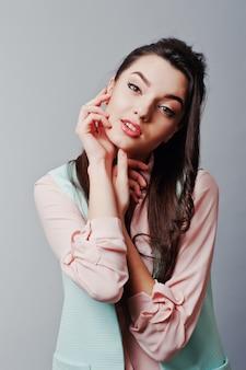 Крупным планом лицо портрет молодой брюнетки девушки, одетой в розовую блузку, бирюзовый жакет, рваные джинсы