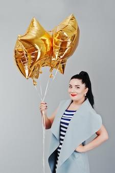 Молодая улыбающаяся женщина с золотыми шарами