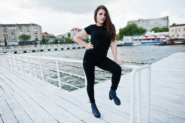 Молодая девушка в черной одежде позирует на пирсе