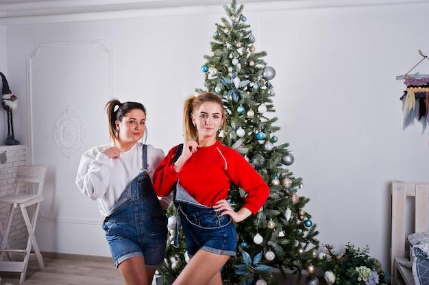 Две веселые красивые подружки носят в комбинезонах джинсовые шорты и гетры на фоне новогодней елки