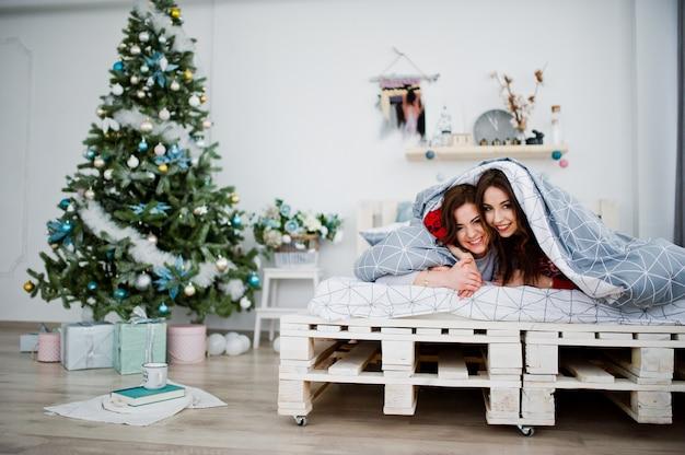 Две подружки надевают зимние свитера, развлекаясь на кровати в комнате с рождественскими украшениями.