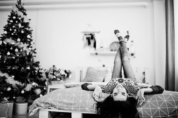 クリスマスツリーのある部屋の冬のセーターベッドに女の子の摩耗。