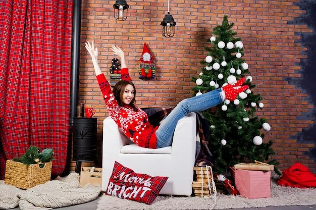 クリスマスの装飾が付いている部屋で冬のセーターを着る少女。