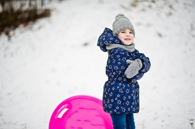 Милая маленькая девочка с санями блюдце на открытом воздухе на зимний день.