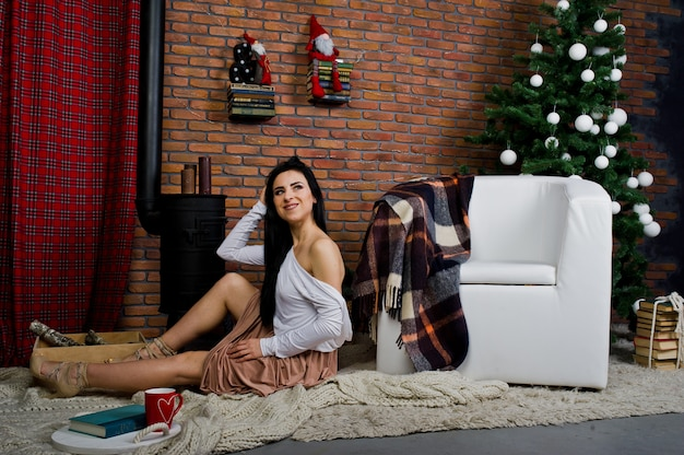 レンガのスタジオルームでクリスマスデコレーションと新年の木の近くでポーズのドレスのブルネットの少女。