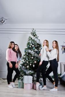 Четыре милые друзья девушки носят на теплые свитера, черные штаны против дерева с рождественские украшения в белой комнате.