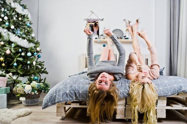 エレガントな金髪の少女は、新年のツリーに対してベッドの上に座って暖かいチュニックに着用します。