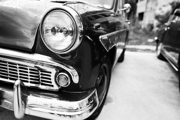 古いビンテージ車のヘッドライトをクローズアップ。白黒写真