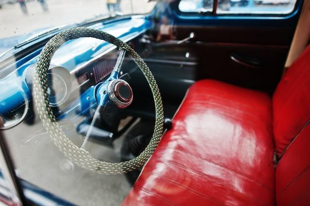 古いビンテージレトロな車の赤い革の座席とインテリアとステアリングホイール