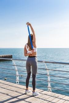 ストレッチ体操を行うスポーツウェアの女性。