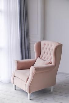 Розовое кресло в гостиной возле окна.