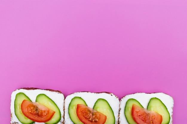 野菜きゅうりと紫色の背景にトマトのサンドイッチ。