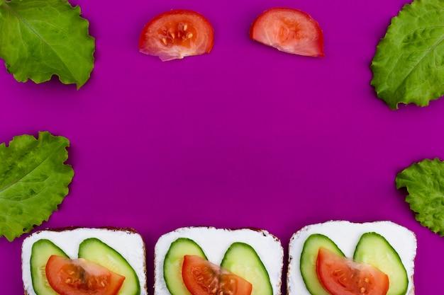 紫色の背景にキュウリとトマトのサンドイッチパン。