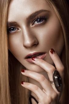 健康な肌と髪、赤いマニキュア、スタジオでポーズ美しい金髪の女性